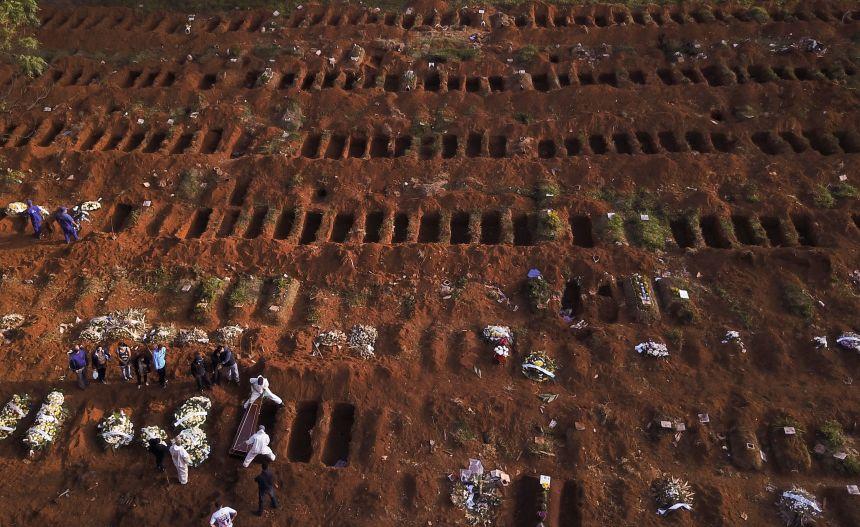 Sepultadores com trajes de proteção enterram vítima de Covid-19 no cemitério de Vila Formosa, em São Paulo
